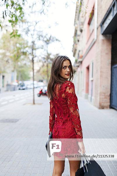 Schöne junge Frau in rotem Kleid mit Einkaufstaschen