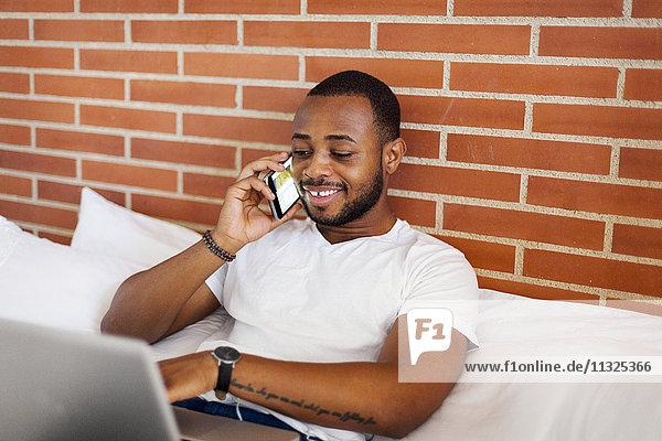 Lächelnder junger Mann im Bett mit Laptop und Handy