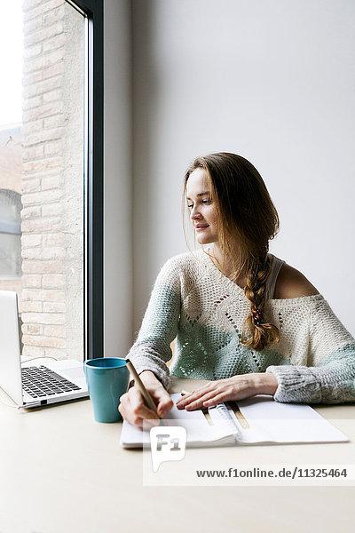 Junge Frau bei der Arbeit mit dem Laptop zu Hause