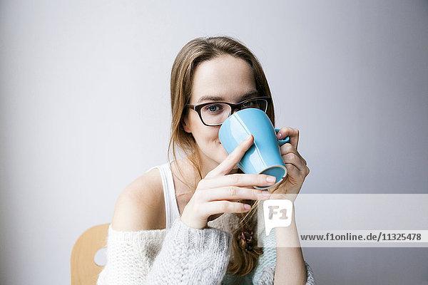 Junge Frau zu Hause beim Kaffeetrinken