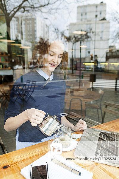 Lächelnde junge Frau mit Laptop und Tasse Tee im Cafe