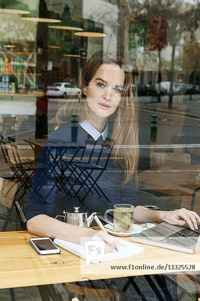 Junge Frau mit Laptop und Tasse Tee im Café Junge Frau mit Laptop und Tasse Tee im Café