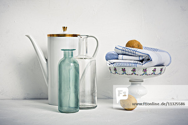 Still life with coffee pot  glass bottles  bowl  towel and lemons
