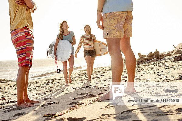 Glückliche Freunde mit Surfbrettern am Strand