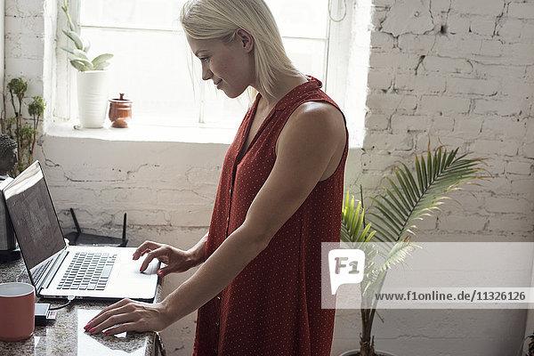 Lächelnde junge Frau mit Laptop im Loft