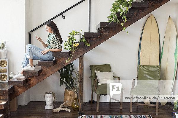 Junge Frau sitzt auf einer Treppe in einem Loft und schaut auf das Handy. Junge Frau sitzt auf einer Treppe in einem Loft und schaut auf das Handy.