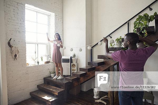Junges Paar schmückt Loft mit Feenlicht