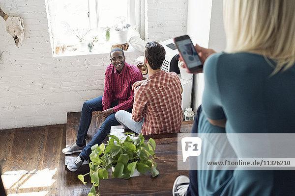 Zwei Männer sitzen auf einer Treppe in einem Loft mit einer Frau  die ein Handy benutzt.