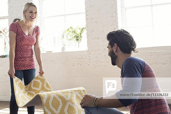 Junges Paar legt Teppich in ein Loft
