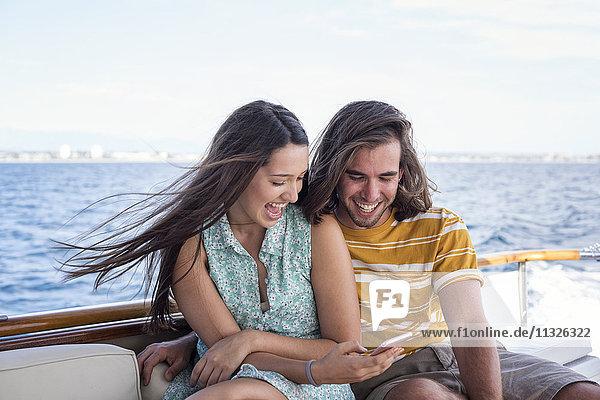 Glückliches Paar auf einer Bootsfahrt mit Blick aufs Handy