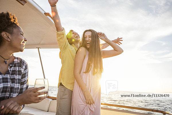 Glückliche Freunde beim Feiern auf einer Bootsfahrt