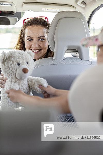 Mutter schaut sich die Tochter an  die mit dem Teddybär spielt und einen Roadtrip macht.