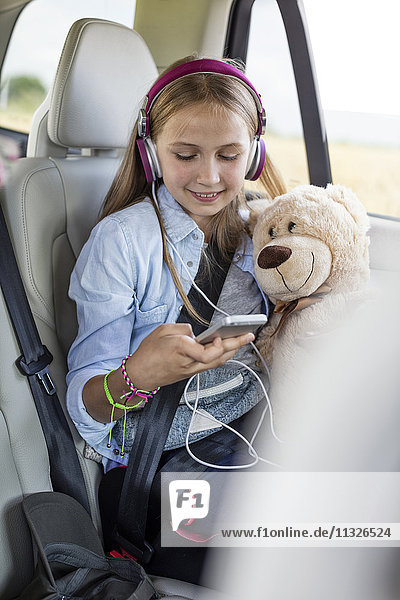 Mädchen im Auto sitzend  Teddybär haltend und Musik hörend