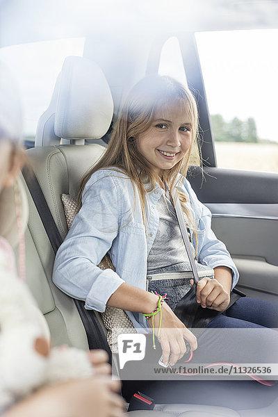 Mädchen sitzt im Auto und schnallt sich an.