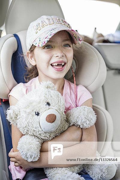 Mädchen im Auto sitzend  Teddybär haltend
