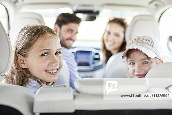 Glückliche Familie bei einem Roadtrip  Blick über die Schulter auf die Kamera