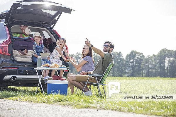 Glückliche Familie auf einem Roadtrip mit Pause am Straßenrand