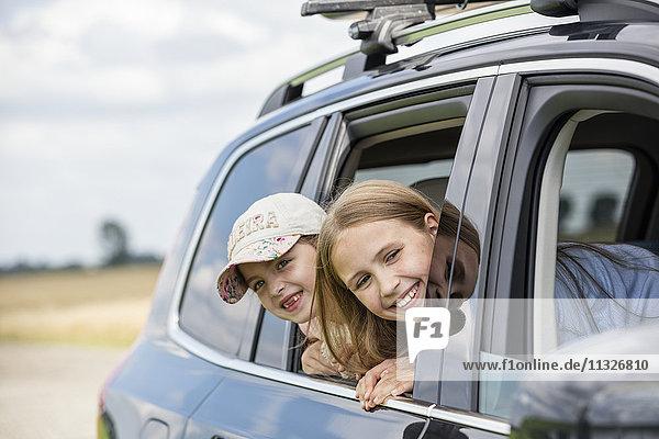 Mädchen sitzen im Auto und schauen aus dem Fenster.
