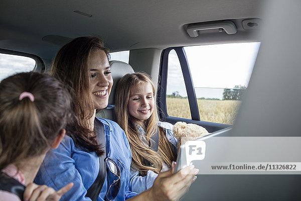 Mutter und Töchter sitzen im Auto und schauen sich das digitale Tablett an.