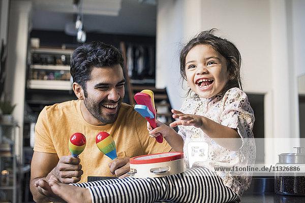 Vater und Tochter musizieren in der Küche