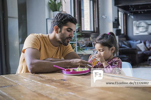 Vater füttert Tochter in der Küche