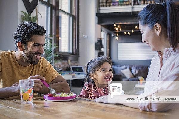 Mutter und Vater füttern ihre kleine Tochter in der Küche.