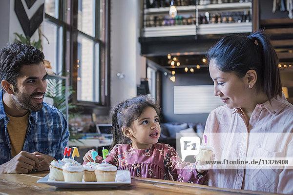 Mutter und Vater essen Geburtstagskuchen mit ihrer kleinen Tochter