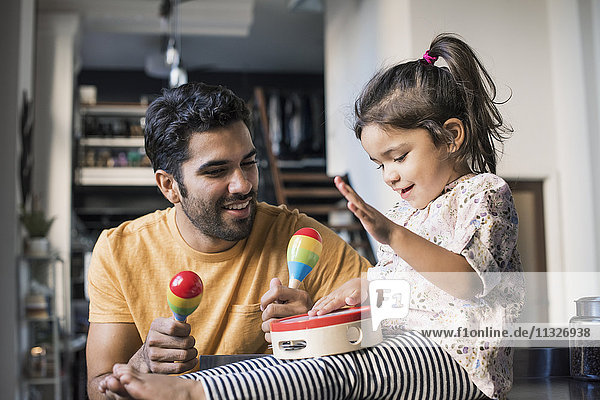 Father and daughter playing music in kitchen