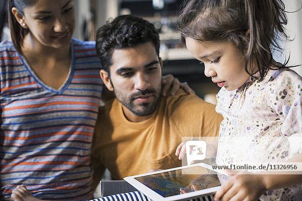 Mutter und Vater beobachten Tochter mit digitalem Tablett