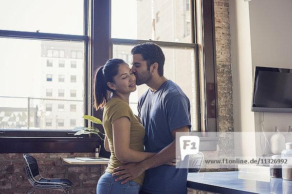 Junges Paar beim Küssen in der Küche