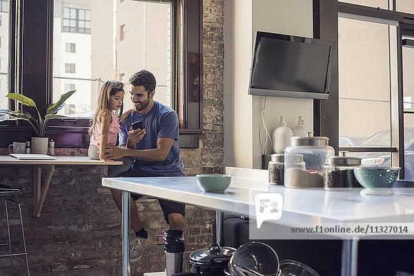 Vater mit Tochter mit Smartphone in der Küche
