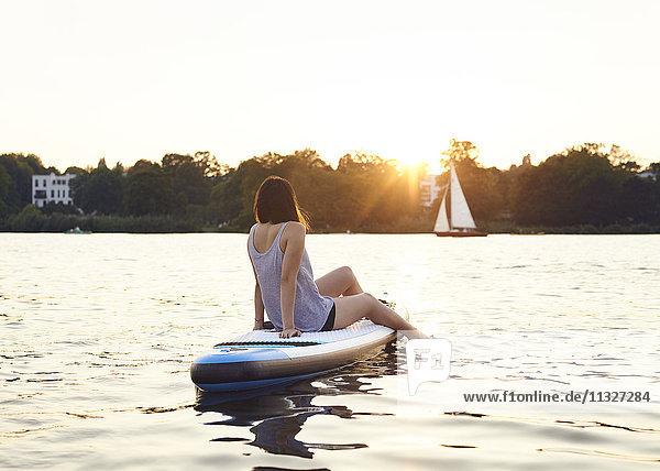Deutschland  Hamburg  Junge Frau auf dem Paddelbrett genießt den Sommer