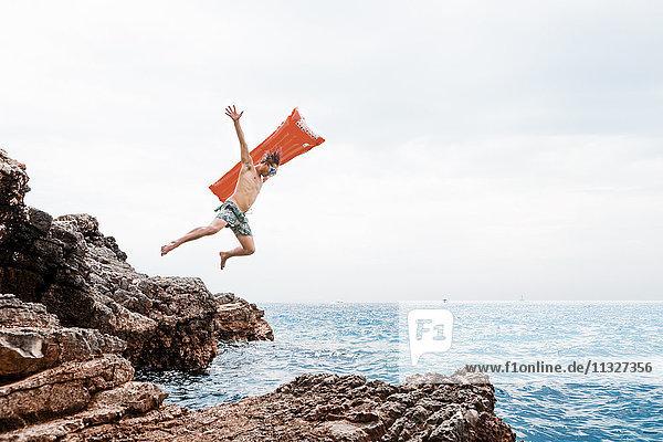 Mann mit Luftmatratze springt vom Felsen ins Meer