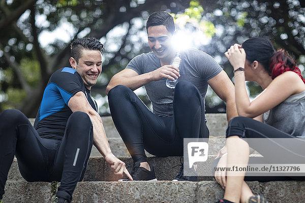 Freunde  die eine Pause im Fitnesspark machen  auf der Treppe sitzend
