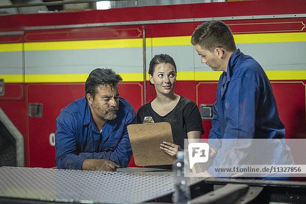 Mechaniker in der Feuerwehrwerkstatt beim Lesen der Checkliste