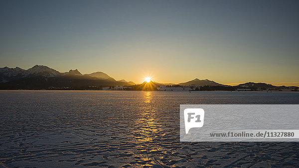ice covered Hopfensee lake at sunset