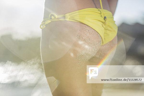 Nahaufnahme einer jungen Frau mit gelbem Tanga am Strand