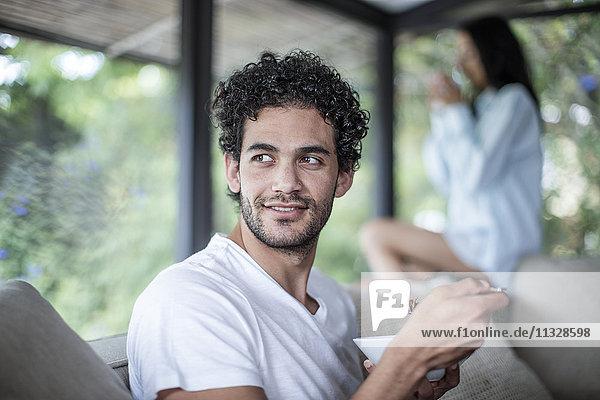 Junger Mann isst zu Hause Getreide mit Frau im Hintergrund
