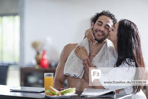 Junge Frau küsst Freund zu Hause während des Frühstücks