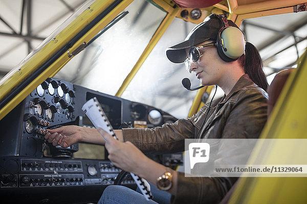 Pilotin bei der Inspektion eines Leichtflugzeugcockpits
