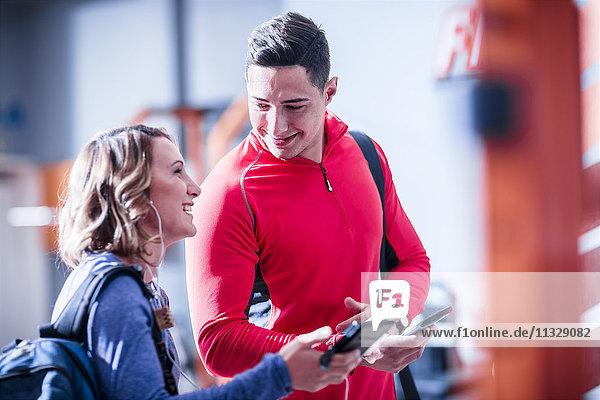 Junger Mann und Frau mit Handys und Ohrhörern im Fitnessstudio