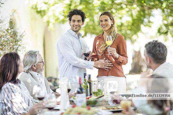 Ein junges Paar  das einen Toast ausspricht  mit der Ankündigung einer Schwangerschaft für die Familie während des Mittagessens außerhalb der Familie.