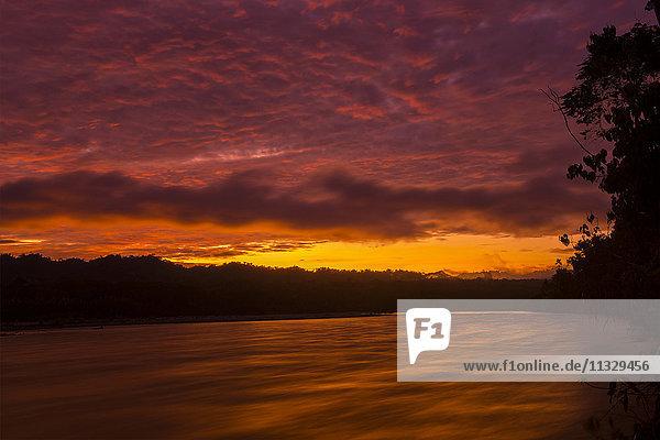 sunset over Madre de Dios river in Manu National Park in Peru