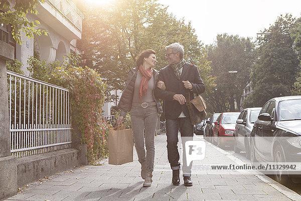 Lächelndes reifes Paar  das auf dem Bürgersteig geht