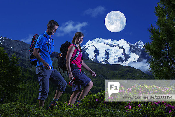 Group hiking at night with full moon near Gibidum in Valais