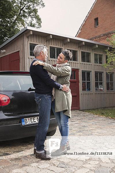 Glückliches Paar umarmt mit dem Auto gegen Haus