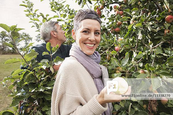 Porträt einer glücklichen Frau beim Apfelessen im Obstgarten