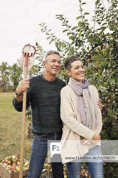 Glückliches Paar steht mit Obstpflücker im Apfelgarten