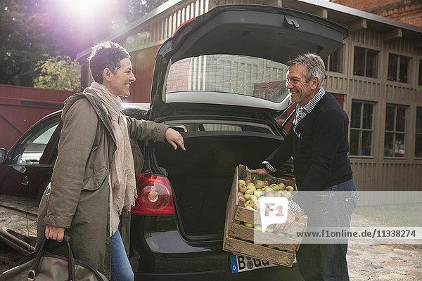 Glückliche Frau schaut den Mann an  der die Apfelkiste in den Kofferraum legt