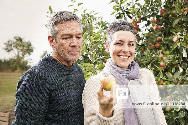 Porträt einer glücklichen Frau mit Apfel von Mann im Obstgarten
